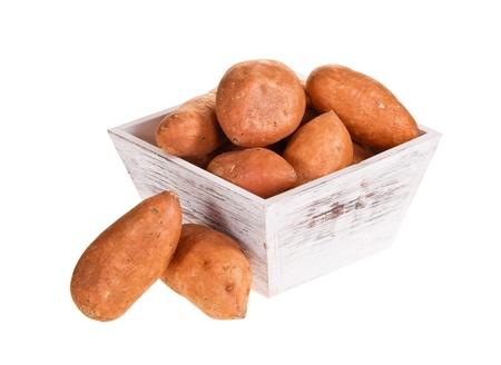 camote: Las patatas dulces, rico en vitaminas y minerales, en un recipiente de madera blanca aislado más de blanco.