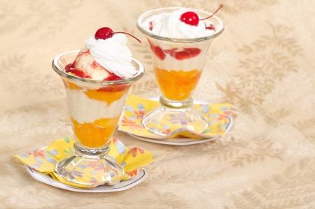 melba: Vanilla peach melba helado con crema batida y cerezas en recipientes de vidrio