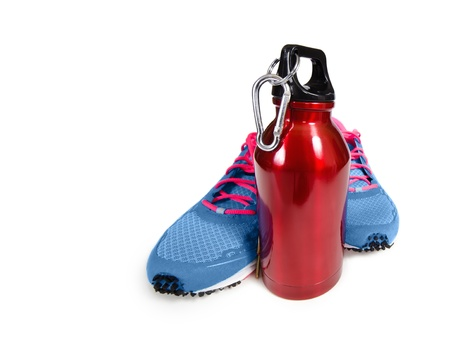 Red stainless steel water bottle with running shoes over white  Exercise and hydration concept