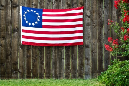 13: 13 Star American flag, the Betsy Ross flag, displayed on rustic wooden fence