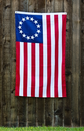 13 Star American flag, the Betsy Ross flag, displayed on rustic wooden fence photo