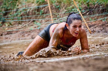 Dallas, Verenigde Staten - 15 september 2012 - Mud ras deelnemer aan een modderpoel. Dash of the Titans Dallas Texas Mud Run Race.