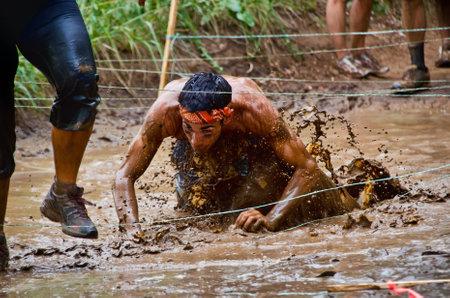 Dallas, USA - September 15, 2012 - Mud race participant crawling through a mud pit. Dash of the Titans Dallas Texas Mud Run Race.