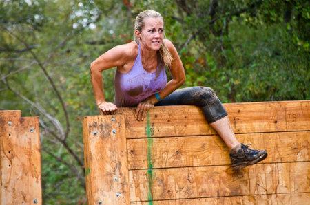 Dallas, USA - September 15, 2012 - Mud race participant climbing over an obstacle. Dash of the Titans Dallas Texas Mud Run Race.
