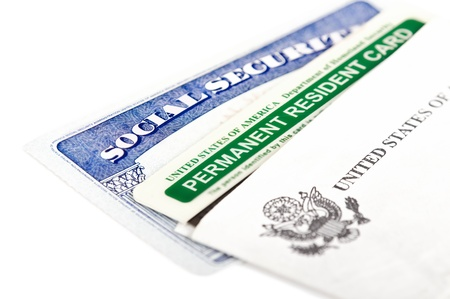 social security: United States of America social security and green card on white background  Immigration concept  Closeup with shallow depth of field