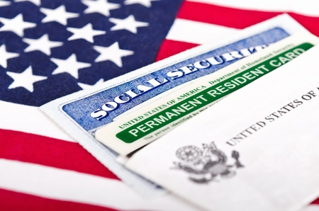 illegal alien: United States of America social security and green card with US flag on the background  Immigration concept  Closeup with shallow depth of field