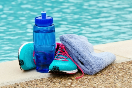 Blue water bottle with running shoes and towel by pool  Exercise and hydration concept  Copy space