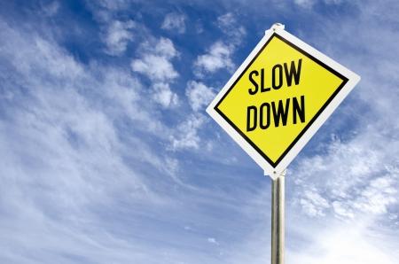 雲の背景が付いている青い空にした遅いダウン黄色道路標識します。 写真素材