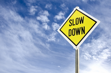 Slow Down yellow road sign on blue sky with clouds background photo