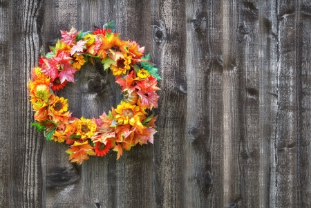 Autumn flower wreath hanging on rustic wooden fence photo