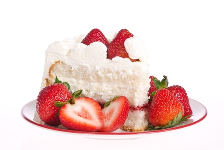Slice of homemade strawberry whipped cream cake with strawberries on plate  photo
