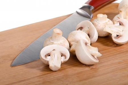Fresh mushrooms sliced on a wooden cutting board with kitchen knife, shallow depth of field photo