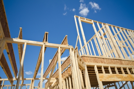 residential home: New residential construction home framing against blue sky