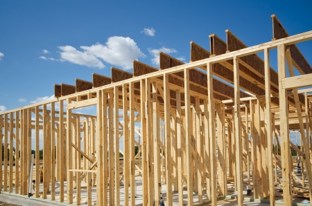 New residential construction home framing against blue sky photo