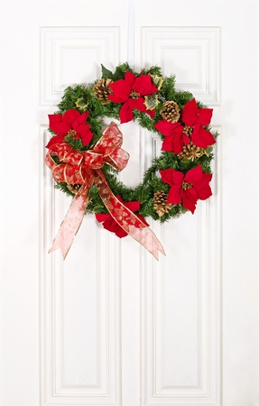 Christmas flower wreath hanging on white wood door photo