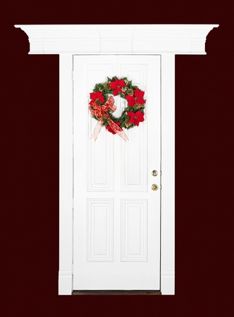 door knob: Christmas flower wreath hanging on white wood door with decorative frame, isolated over dark red
