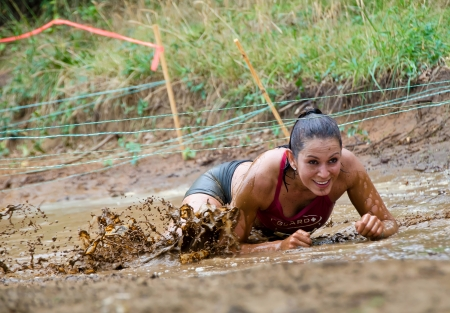 participant: Dallas, USA - September 15, 2012 - Smiling female mud race participant crawls under the wires at a mud pit  Dash of the Titans Dallas Texas Mud Run Race