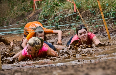 Dallas, USA - September 15, 2012 - Female participants crawl under the wires at a mud pit  Dash of the Titans Dallas Texas Mud Run Race  에디토리얼