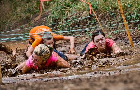 Dallas, USA - 15. September 2012 - Weibliche Teilnehmer unter den Drähten kriechen in einem Schlammloch Dash of the Titans Dallas Texas Mud Run Rennen Standard-Bild - 21840795