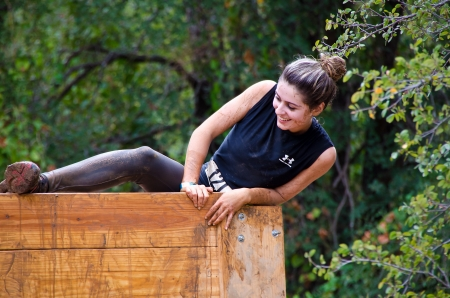 participant: Dallas, USA - September 15, 2012 - Smiling female mud race participant climbing over an obstacle  Dash of the Titans Dallas Texas Mud Run Race  Editorial