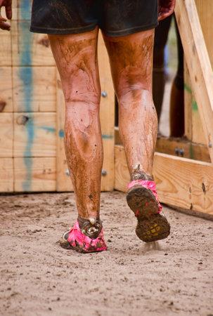 participant: Dallas, USA - September 15, 2012 - Closeup of mud run participant approaching a wall obstacle  Dash of the Titans Dallas Texas Mud Run Race