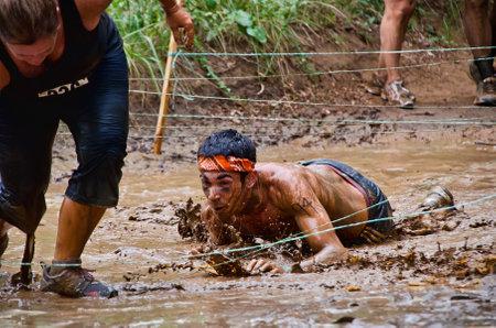 Dallas, USA - September 15, 2012 - Mud run race participant crawling through a mud pit Dash of the Titans Dallas Texas Mud Run Race