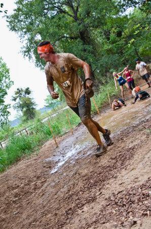 participant: Dallas, USA - September 15, 2012 - Mud run race participant passing through a mud pit  Dash of the Titans Dallas Texas Mud Run Race