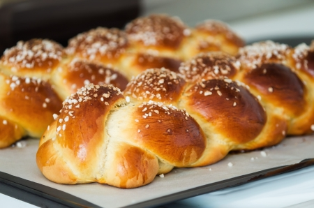 Freshly baked sweet braided bread loaf on a baking sheet, shallow depth of field  Stockfoto
