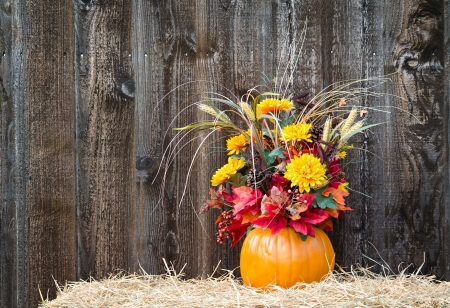 Pumpkin flower arrangement on hay against rustic wooden background Stock Photo - 23301783