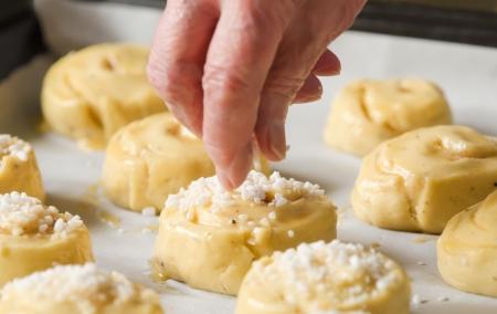 haciendo pan: Primer plano de una persona mayor de azúcar rociada sobre rodillos dulces en una bandeja para hornear