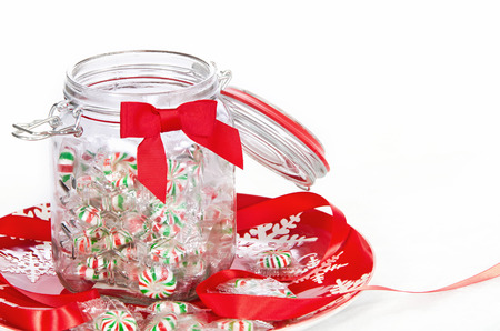 peppermint candy: Pinwheel Christmas candies in a glass jar, displayed on red holiday plate