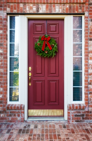 Christmas wreath hanging on a red wooden door of a brick house