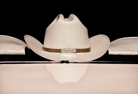 western attire: Cowboy hat displayed on the back of a car window against dark background, sepia color Stock Photo