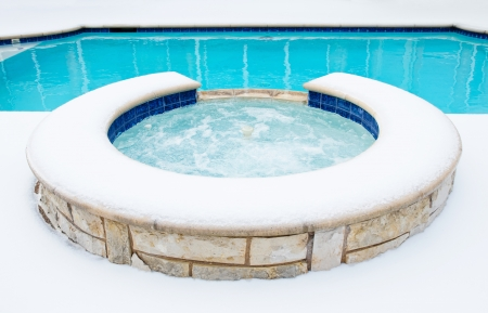 Outdoor residential hot tub or spa by swimming pool surrounded by snow in the winter