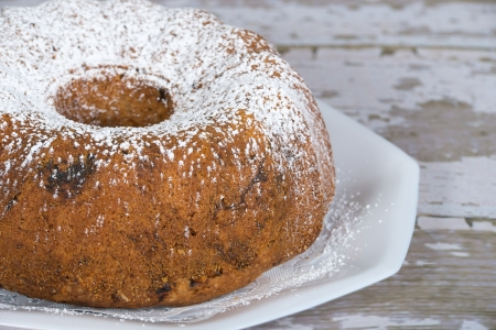 Golden brown homemade bundt cake with prunes and spices. Gray , shallow depth of field. Imagens