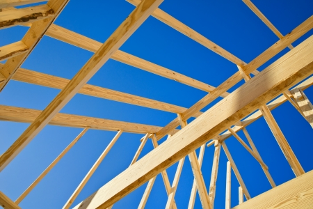 frame of wood: New construction home framing against blue sky, closeup of ceiling frame. Stock Photo