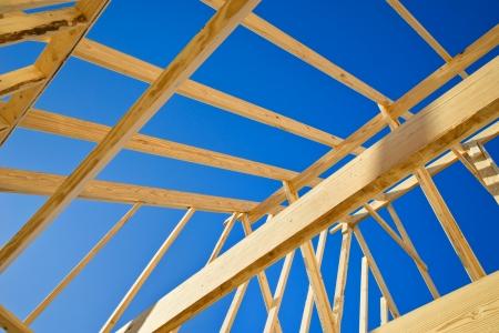 frame wood: New construction home framing against blue sky, closeup of ceiling frame. Stock Photo