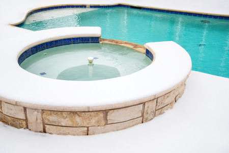 Outdoor hot tub or spa by swimming pool surrounded by snow in the winter Stock Photo