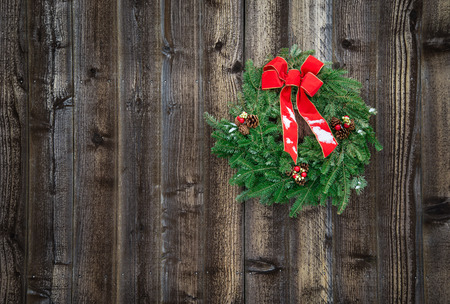 Holiday wreath hanging on rustic wooden fence photo