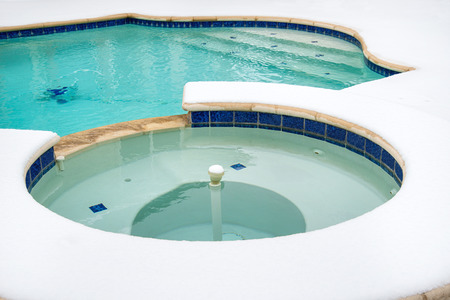 Outdoor hot tub or spa by swimming pool surrounded by snow in the winter Stock fotó