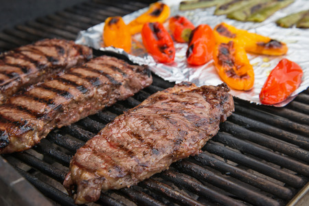 grate: Steaks cooking on the grill  Colorful peppers on foil on the background