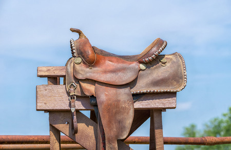 Leather horse saddle displayed on a stand against blue sky