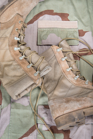 Old combat boots against camouflage military desert uniform photo