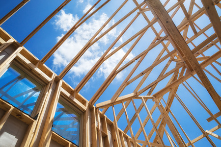 residential construction: New construction home framing against blue sky, closeup of ceiling frame. Stock Photo