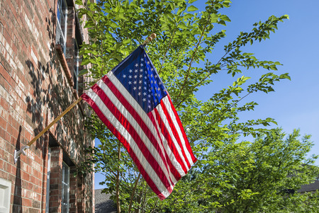 Patriotic American flag in front of a brick home, trees and blue sky background photo