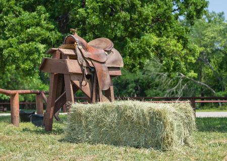 wildwest: Cavallo da sella in pelle visualizzata su un supporto di legno e una balla di fieno Archivio Fotografico
