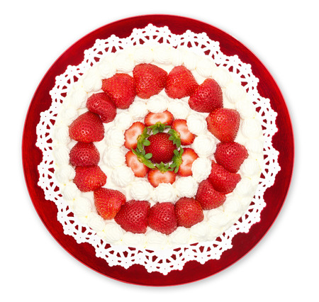 Homemade strawberry whipped cream cake displayed on a red plate, isolated over white photo