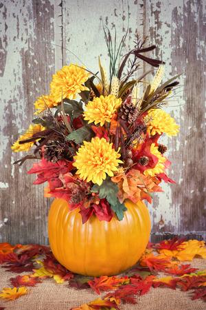Autumn pumpkin flower arrangement centerpiece, rustic background, vintage filter effects
