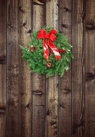 Christmas wreath hanging on rustic wooden fence photo