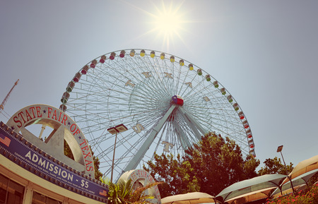 DALLAS, TX, - July 6, 2014: Texas Star, the largest ferris wheel in North America, rises above the horizon at Fair Park in Dallas, Texas. Fisheye capture with vintage filter effects. Reklamní fotografie - 31187491